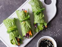 Rolls from lettuce leaf with vegetables and rice noodles and soy sauce with sesame. Vegetarian and vegan rolls with lettuce, carro. Ts, red cabbage, rice noodles royalty free stock photo