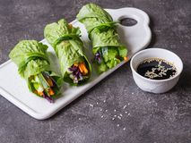 Rolls from lettuce leaf with vegetables and rice noodles and soy sauce with sesame. Vegetarian and vegan rolls with lettuce, carro. Ts, red cabbage, rice noodles royalty free stock image