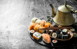 Rolls and maki on a stone stand with green tea in the teapot. On dark rustic background stock photos