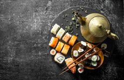 Rolls and maki on a stone stand with green tea in the teapot. On dark rustic background stock photo