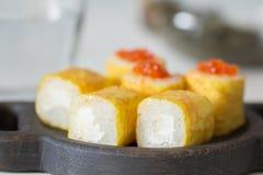 Rolls med kaviaren i en omelett på ett träbräde Fotografering för Bildbyråer