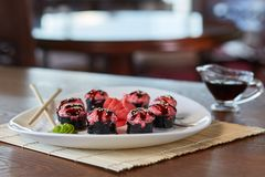 Rolls med ris, norialger, den röda kaviaren, sesam, på en platta med wasabi, inlagd ginge, pinnar som är närliggande är soya arkivfoto
