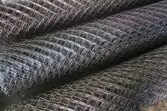Rolls of the metallic net. On asphalt background Stock Photos