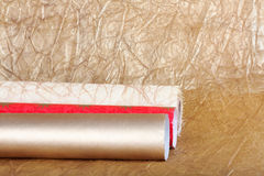 Rolls of multicolored wrapping paper for gifts on gold backgroun Royalty Free Stock Images