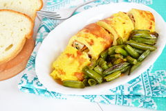Rolls of omelette with cheese on a plate, fried green beans. Omelette recipe. Eggs omelet. Stuffed omelette photo. Omelet with stuffing. Omelet with cheese royalty free stock images