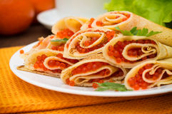 Rolls pancakes with red caviar. Russian cuisine. Flat lay. Maslenitsa. Wooden background. Close-up. Rolls pancakes with red caviar. Russian cuisine. Flat lay Stock Photo