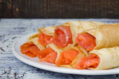 Rolls from pancakes with salmon on the white ceramic plate Royalty Free Stock Images