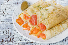 Rolls from pancakes with salmon on the white ceramic plate Royalty Free Stock Photography