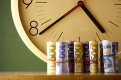 Rolls of paper money an analog clock. Rolls of paper money and an analog clock stock photos