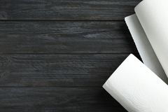 Rolls of paper towels on black wooden table. Space for text. Rolls of paper towels on black wooden table, top view. Space for text stock image
