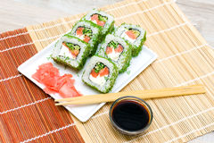 Rolls, pickled ginger and chopsticks on a white plate on a woode Royalty Free Stock Photos