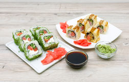 Rolls, pickled ginger, soy sauce and chopsticks on a white plate Stock Photos
