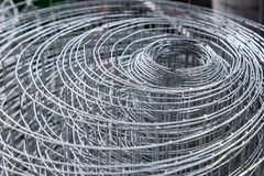 Rolls of plastic chicken wire meshes, aluminum wire meshes, and. Thin galvanized metal sheets stacking up at a shop stock photo