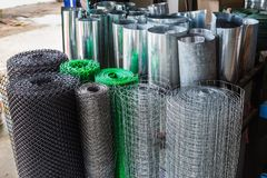 Rolls of plastic chicken wire meshes, aluminum wire meshes, and. Thin galvanized metal sheets stacking up at a shop stock photos