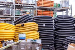 Rolls of plastic pipes in a warehouse yard. Rolls of plastic and rubber pipes or tubes stacked high in a warehouse or factory yard for use to supply utilities in Royalty Free Stock Photo