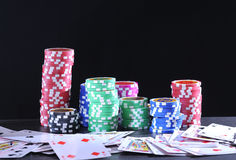 Rolls of poker chips and cards on black background Royalty Free Stock Photo