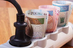 Rolls of polish currency money in electrical power strip with connected plug, energy costs. Rolls of polish currency money in electrical extension with connected stock image