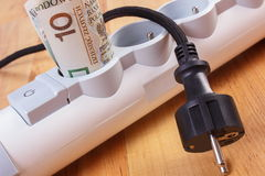 Rolls of polish currency money in electrical power strip and disconnected plug, energy costs Stock Photo