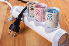 Rolls of polish currency money in electrical power strip and disconnected plug, energy costs. Rolls of polish currency money in electrical extension and royalty free stock photography