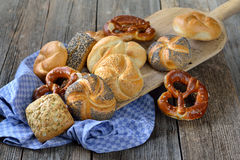 Rolls and pretzels. Fresh Bavarian rolls and pretzels on a vintage baking board stock images