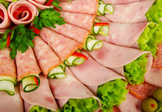 Rolls of processed meat garnished with lettuce. Close-up of rolls of ham and salami decorated with green olives, leaves of lettuce, slices of cucumber and leaves Royalty Free Stock Photos