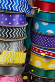 Rolls of ribbon background. Stacks of rolled ribbon with sewing pins holding them Stock Image