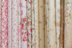 Rolls of romatic flowery printed cloths. Rolls of cloth printed with various flowery patterns white, beige, red, pink and light green Royalty Free Stock Images