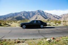 Rolls Royce путешествуя на проселочной дороге с горами в предпосылке стоковые изображения rf