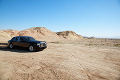 Rolls Royce car leaving trail of black oil behind on unpaved road Royalty Free Stock Photography