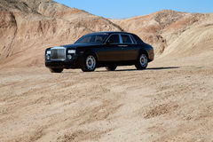 Rolls Royce car parked on unpaved road with mountains in background Royalty Free Stock Photos