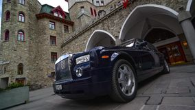 Rolls Royce in front of Badrutt Palace Hotel. Time lapse of camera pan R to L past a Rolls Royce to the Badrutt Palace Hotel in St. Moritz Switzerland stock video