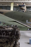 Rolls Royce Merlin engine broken in foreground with blurred Hawker Hurricane in background. Pilot displayed in cockpit pointing Royalty Free Stock Photos