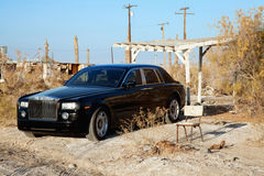 Rolls Royce parked next to broken chair in abandoned village Stock Photos