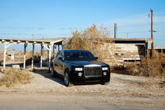 Rolls Royce parked on roadside in front of abandoned house Stock Photos