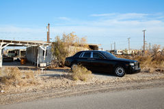 Rolls Royce parked on side of road near abandoned houses Royalty Free Stock Photography