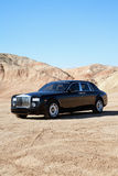Rolls Royce parked on unpaved road with clear sky Stock Photography