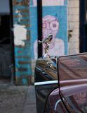 Rolls Royce Silver Spirit emblem. Silver Spirit emblem on a parked Rolls Royce in one of the poorest areas of East London with some street art in the background Stock Image