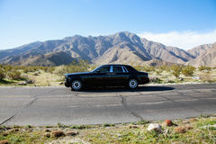 Rolls Royce travelling on country road with mountains in background Royalty Free Stock Images