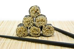 Rolls with sesame and sticks. Japanese rolls with sesame and sticks on the mat Royalty Free Stock Photography