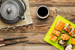 Rolls with soy sauce, chopstick and teapot. Yummy food stock photos