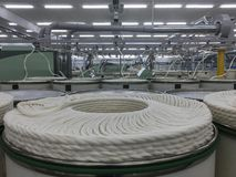 Rolls of spun cotton in a textile factory. A spinning machine with rolls of spun cotton in a textile Royalty Free Stock Photography
