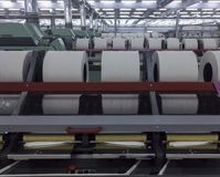 Rolls of spun cotton in a textile factory. A spinning machine with rolls of spun cotton in a textile Royalty Free Stock Photo