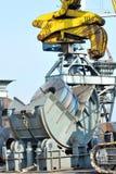 Rolls of steel sheet in harbor. And crane Stock Photos