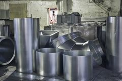Rolls of steel sheet or iron tubed, industrial production of ventilation pipes. In warehouse Royalty Free Stock Photo