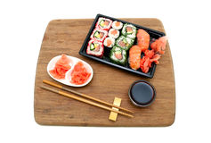 Rolls and sushi on a bamboo board isolated on white background Royalty Free Stock Images