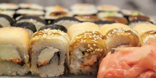 Rolls. Of sushi fish stuffing cheese crab cucumber eel sharp ginger sauce Royalty Free Stock Image