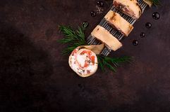 Rolls of thin pancakes with salmon, horseradish cream cheese. Black old background. Top view. Selective focus royalty free stock photos
