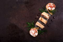 Rolls of thin pancakes with salmon, horseradish cream cheese. Black old background. Top view. Selective focus royalty free stock images