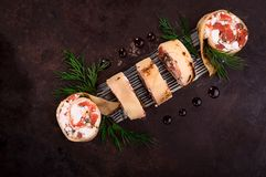 Rolls of thin pancakes with salmon, horseradish cream cheese. Black old background. Top view. Selective focus royalty free stock photo