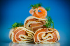 Rolls of thin pancakes with salted red fish Royalty Free Stock Photo